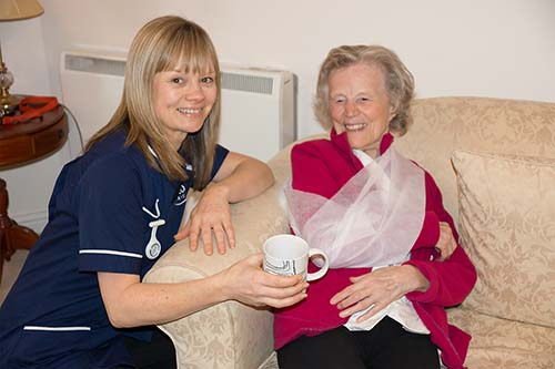 At home carer giving a cup to a patient