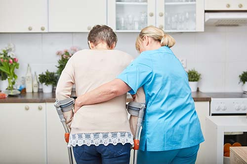 Carer helping patient to walk with crutches